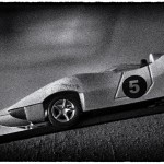Black and white photo of a vintage toy race car.