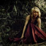 A young woman in a red dress crouching in a dark forest.
