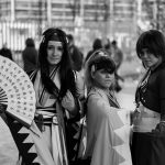 Three teenage girls pose in samurai cosplay outfits.