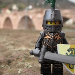 A Lego figurine dressed as a black knight with sword and shield.