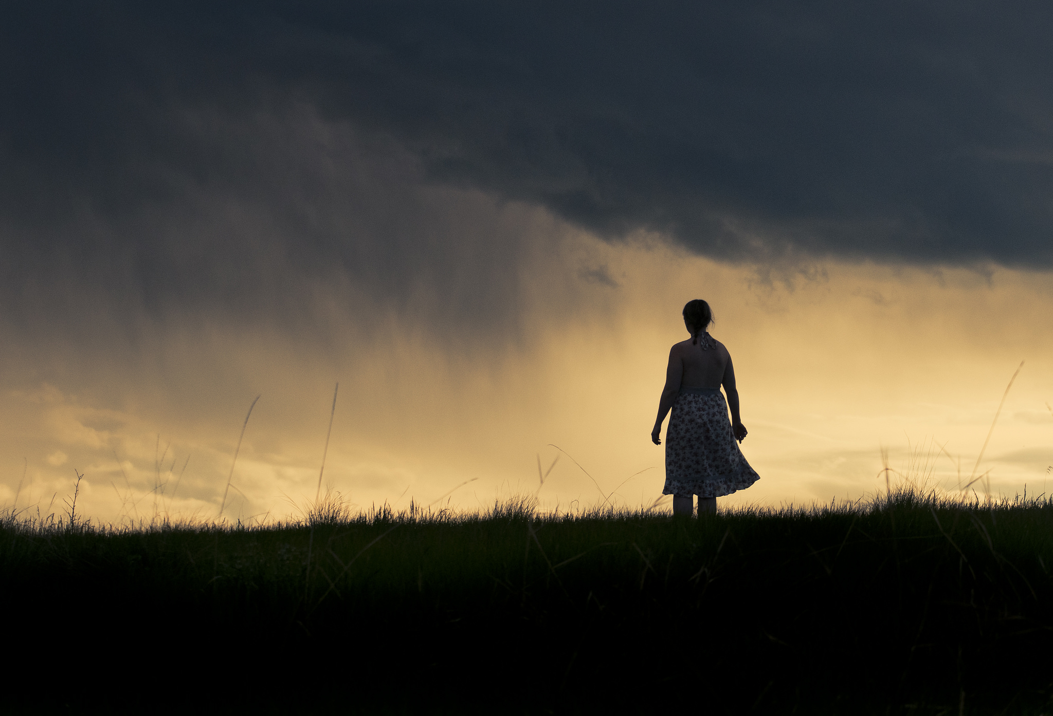 Woman silhouetted by the setting sun, standing on a hill.