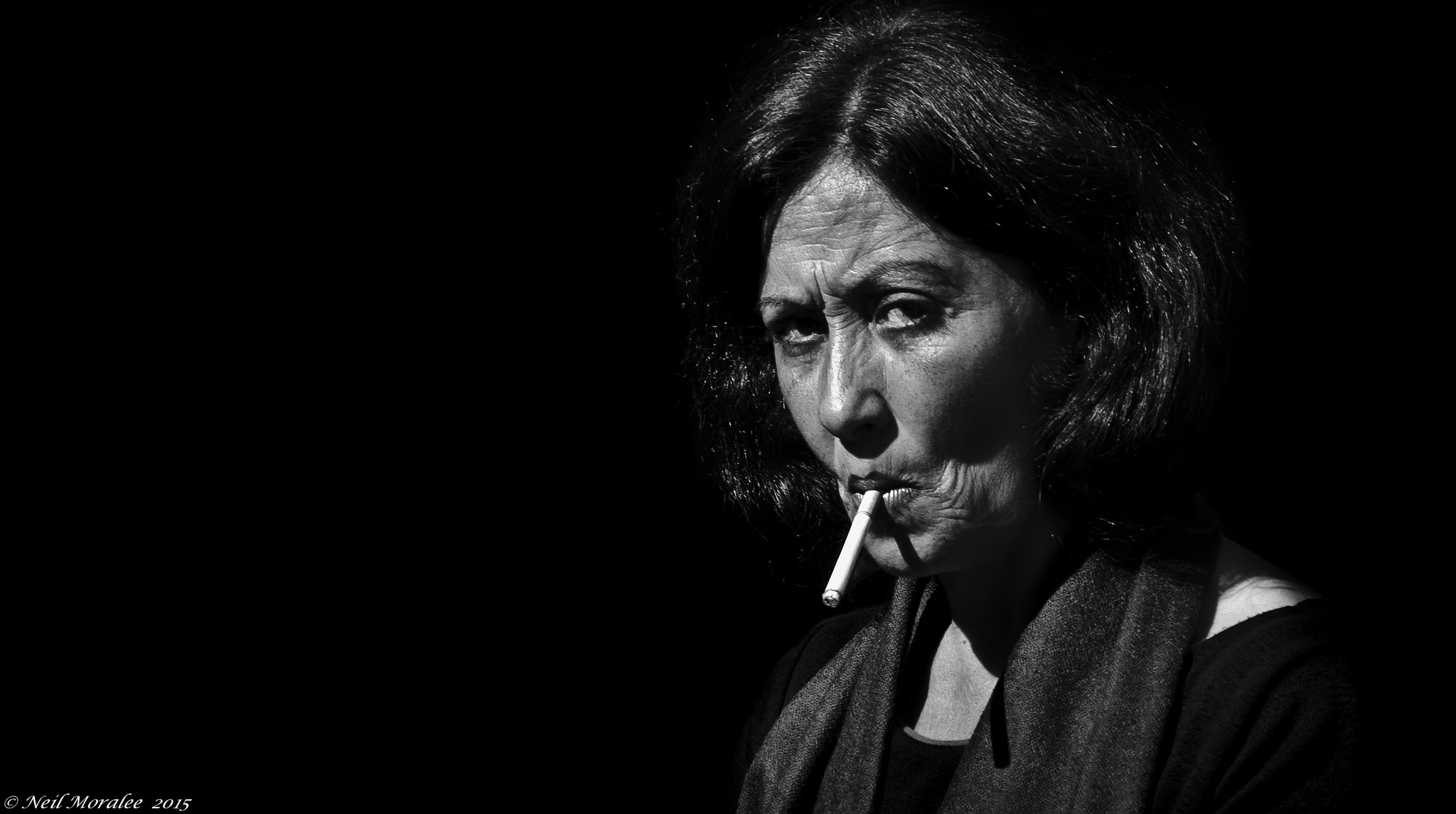 Black and white portrait of a mature woman smoking.