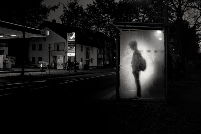 Black and white photo of a boy standing at a bus stop.