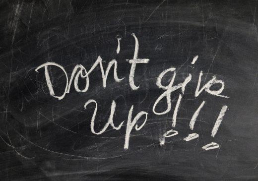 """""""Don't give up!!!"""" written in chalk on a blackboard."""