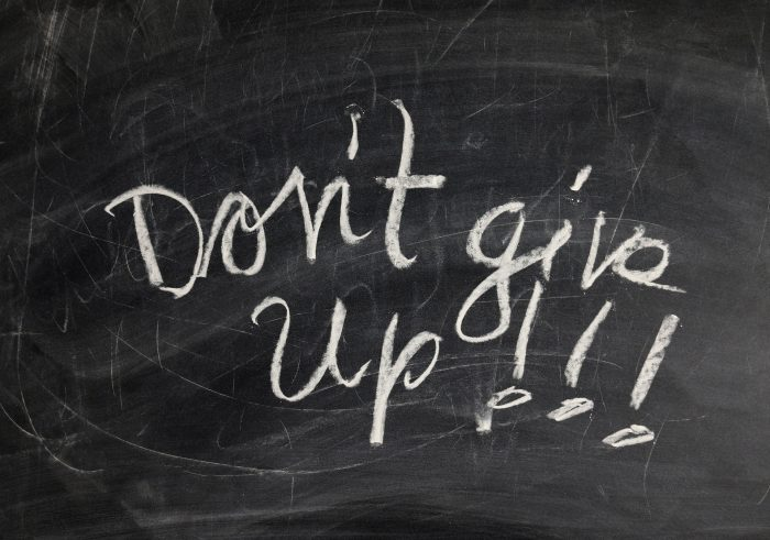 """Don't give up!!!"" written in chalk on a blackboard."