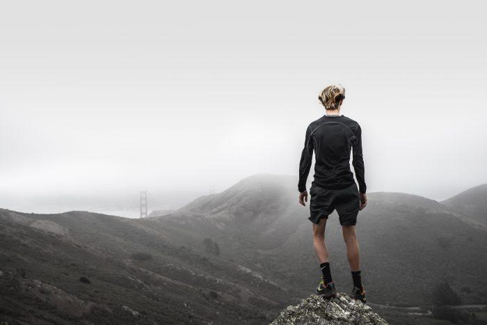 A man in running gear overlooking a mountain range, the tops hidden in clouds.