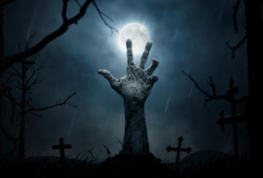 A graveyard with a hand bursting out of the ground. The moon in the background.